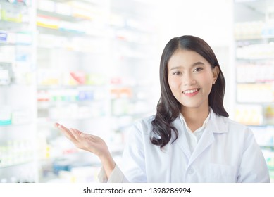Beautiful asian female pharmacist smiling in drugstore