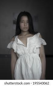 beautiful asian female posing in a white dress