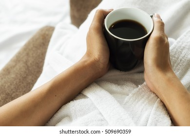 Beautiful asian female sitting on the bed with a cup of coffee. Morning with a book and cup of coffee. Relaxing concept. Retro filter effect,soft focus,selective focus.