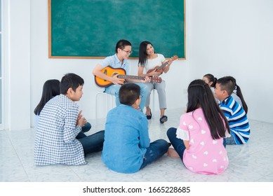 Beautiful asian female teacher playing ukulele with her male student playing guitar in classroom,showing to her students sitting on the floor.