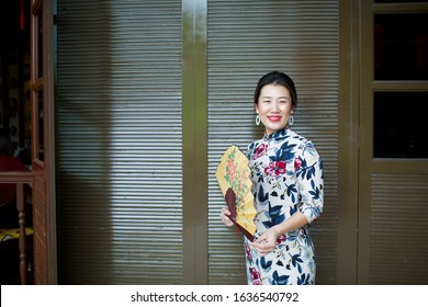 Beautiful Asian female wearing qipao holding hand fan.Flowery cheongsam.China girl with dimples.Lady standing by restaurant window.Chinese New Year celebration.Oriental woman with big smile.