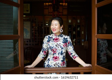 Beautiful Asian female wearing qipao.Flowery cheongsam.China girl with dimples.Lady standing by restaurant window.Chinese New Year celebration.Oriental woman with big smile.