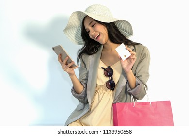 Beautiful Asian female in yellow dress and white hat holding smartphone in one hand and smartcard in another hand with shopping bag feeling happy with smiling face