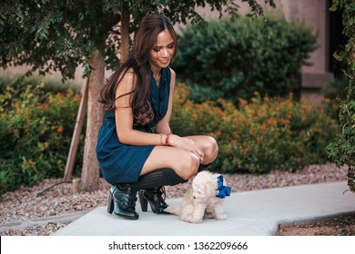 beautiful asian filipino girl in her 20s with long hair wearing a dress and boots kneeling down and looking down next to a cute maltipoo puppy with a blue bow on outside