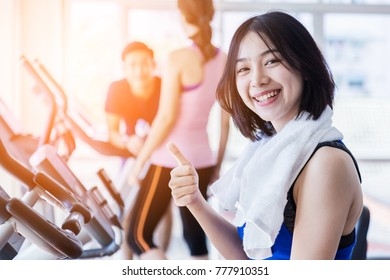 beautiful Asian fitness teenager on bicycle machine doing spinning at fitness.  sport and Healthy concept. Workout with happiness and Cardio ideas.