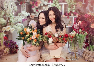 Beautiful asian florist girls making bouquet of flowers on table for sale against floral bokeh background in flower shop indoors. Two attractive asian females florists working in store. 2 playful