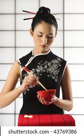beautiful asian girl in calssics oriental dress in act to eat with chopstick