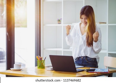 Beautiful Asian girl celebrate with laptop in office.