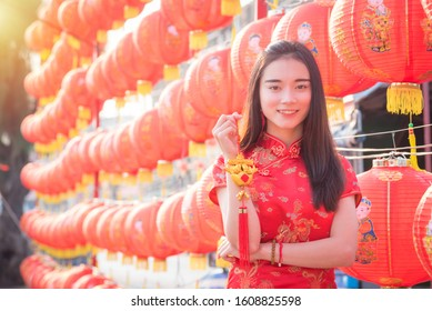 Beautiful asian girl in chinese traditional costume smiling in front of red chinese lantern.Chinese new year concept.
