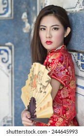Beautiful Asian girl with Chinese traditional dress Cheongsam holding a Chinese Fan