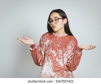 beautiful asian girl compares something in her hands, wears glasses and pink sweater, studio photo on background
