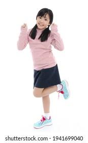 Schönes asiatisches Mädchen, das auf weißem Hintergrund tanzt, einzeln