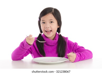 Beautiful asian girl eating with empty white plate on white background isolated
