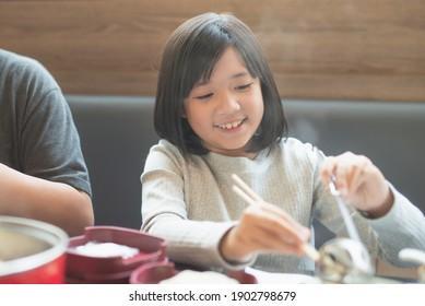 Schönes asiatisches Mädchen, das sukiyaki im japanischen Restaurant isst