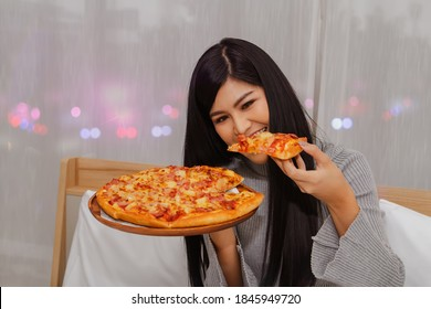 Beautiful Asian girl eats pizza gluttony is dinner, eaten before bedtime, eating in bed in her house with pleasure : Woman orders pizza online for home delivery during Covit-19 epidemic