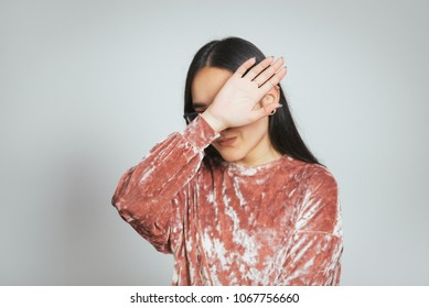 beautiful asian girl embarrassed, wearing glasses and pink sweater, studio photo on background