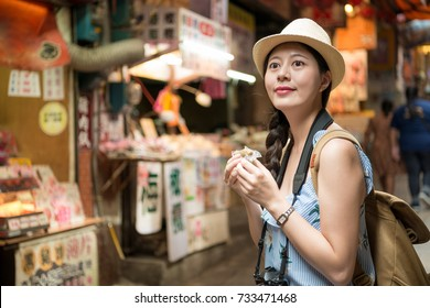 beautiful Asian girl enjoy eating local shop food herbal cake and walking on old street of Taiwan holiday travel in Jiu Fen Town.