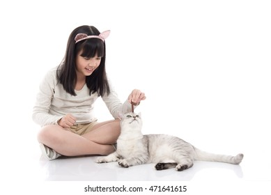 Beautiful Asian girl feeding snack to cute kitten on white background isolated