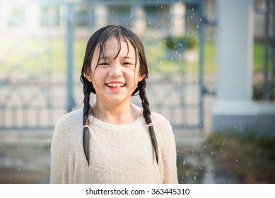 Beautiful asian girl is happy with the rain