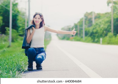 beautiful asian girl hitchhiking on the road ,travel concept