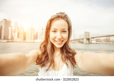 beautiful asian girl holding the camera and taking self portrait in New york. Brooklyn bridge and new york skyline in the background