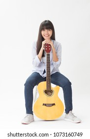 Beautiful asian girl holding guitar in hand on white background