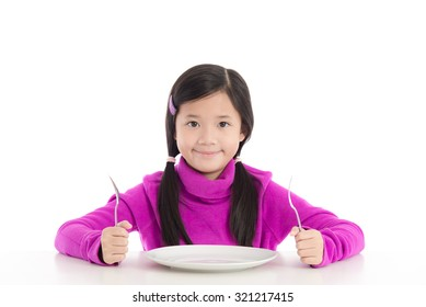 Beautiful asian girl holding a spoon and fork with empty white plate on white background isolated