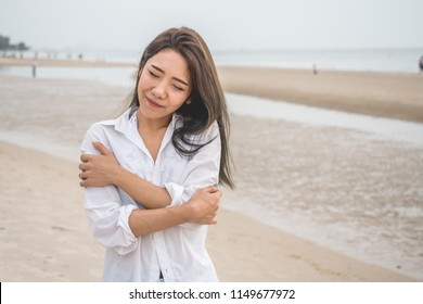 Beautiful Asian girl hugging herself with natural emotional delightful face on the beach, concept for love yourself with copyspace.