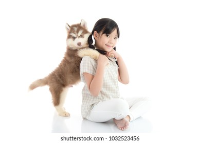 Beautiful asian girl hugging siberian husky puppy on white background isolated