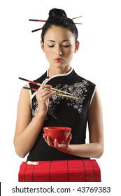 beautiful asian girl in japanese dress eating oriental food from a red cup using chopstick