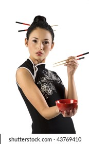 beautiful asian girl in japanese dress and chopstick showing a red cup