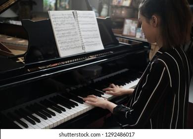 Beautiful asian girl learn to play piano
