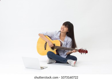 Beautiful asian girl learning to play music online sitting on white background