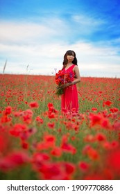 Beautiful Asian girl with long hair in a red dress with a large bouquet of poppies and cornflowers in her hands on the background of a blooming field with wild red flowers.