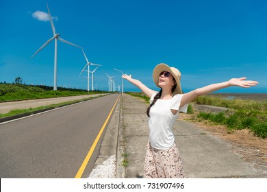 beautiful Asian girl open her hand to enjoy great weather with green energy power on holiday by road beach site with sunshine blue sky.
