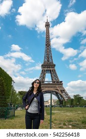 Beautiful Asian girl in Paris with Eiffel tower on background. Young Asian  girl outdoors near the Eiffel tower. Girl in Paris on a sunny spring. Asian girl in Europe. Travel and Lifestyle