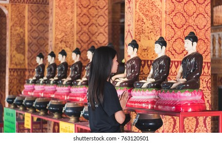 Beautiful asian girl to pay respect and praying Buddhism worshiping Buddha statue with faith