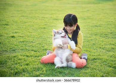 Beautiful asian girl playing with siberian husky puppy in the park