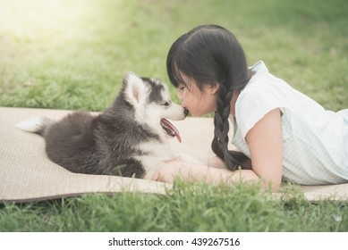 Beautiful asian girl playing with siberian husky puppy in the park,vintage filter