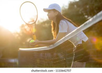 Beautiful Asian girl playing tennis outdoors at sunset