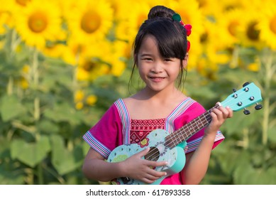 Beautiful asian girl playing ukulele, Outdoor portrait. The back garden is a sunflower garden.
