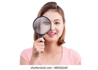 Beautiful asian girl portrait looking through magnifier. Isolated on white.
