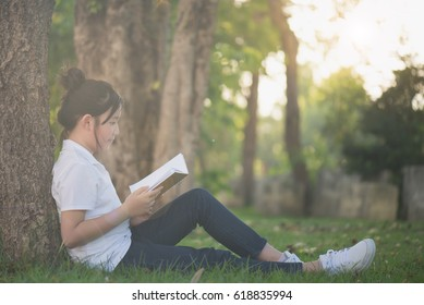 Beautiful Asian Girl reading a book under the tree on summer day