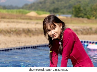 beautiful asian girl in red swimsuit play in the outdoor swimming pool with the village background