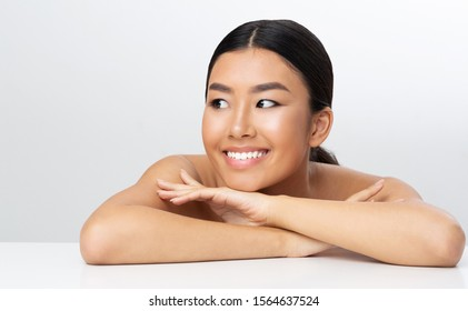 Beautiful asian girl relaxing after massage, leaning on table over light background