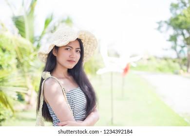 Beautiful asian girl relaxing on a resort wearing a straw hat