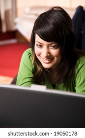 A beautiful asian girl relaxing on the sofa working on laptop