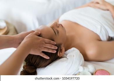 Beautiful Asian girl relaxing receiving facial massage in a spa salon