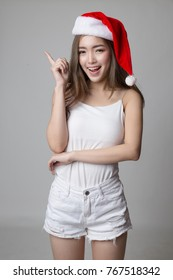Beautiful asian girl with santa hat pointing to copy space