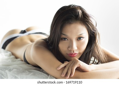 Beautiful asian girl in sexy lingerie posing on bed